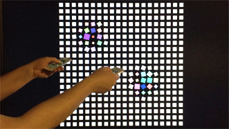 User demonstrating substrate capabilities by pointing two iPhones at a screen, distorting a grid of squares according to the movement of each device