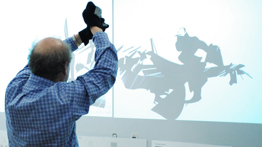 Man holds hands over his head with gestural tracking gloves, making virtual marks with a squeezing gesture