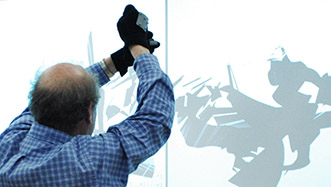 Man creating and drawing virtual marks on a projection screen using gestural tracking software