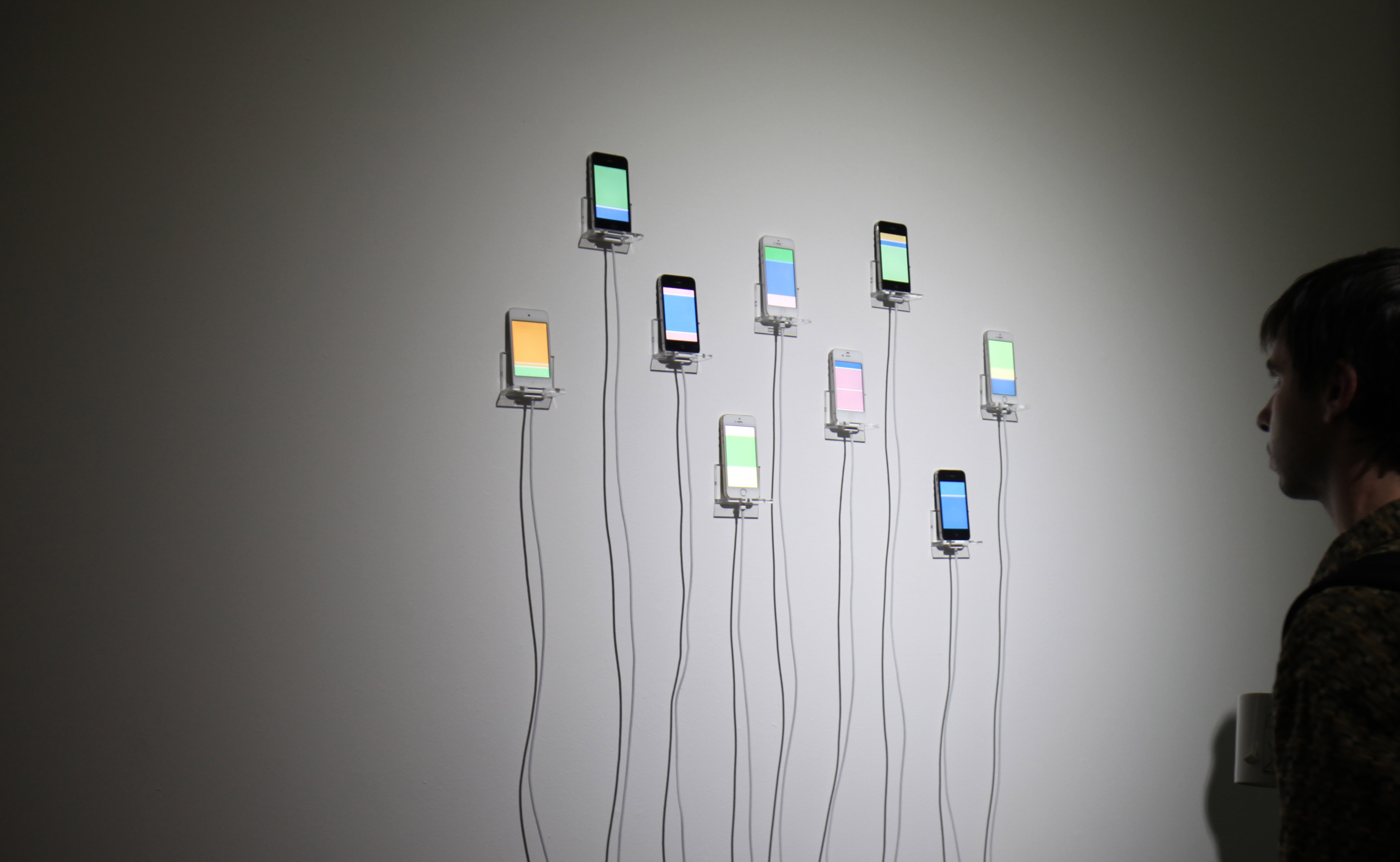 Man observes the iPhones in Infinite Scroll mounted on the wall, each scrolling bright colors
