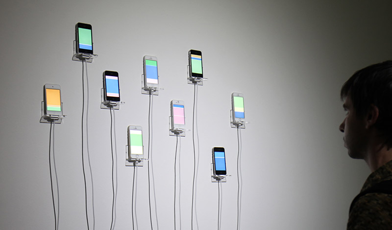 Man observes art installation with nine iPhones mounted on the wall showing blocks of bright colors on their screens, simulating the infinite scrolling motions of social media