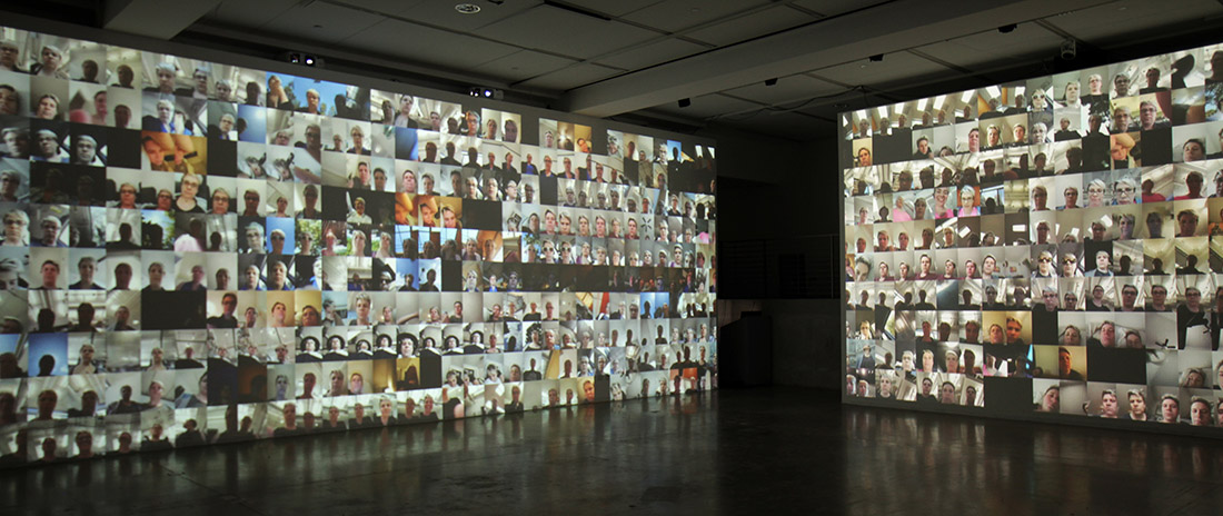Two walls covered in a video projection of a grid of many smartphone selfie camera videos from the same user in phonelovesyoutoo: matrix