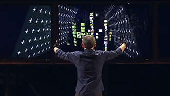 Man demonstrates rummage by controlling two large rectangles on a triptych of computer monitors using his arms outstretched to his side