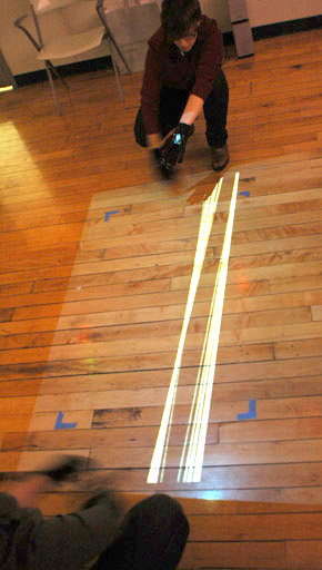 Two users wearing motion capture gloves control white parallel glowing lines on the floor between their hands in tangle