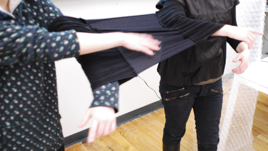 Two users wear a uniquely designed sleeve-garment to link their arms together and constrain their movement while using tangle