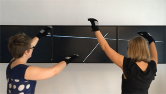 Two performers wearing gesture tracking gloves to draw virtual lines between their hands on a distant screen