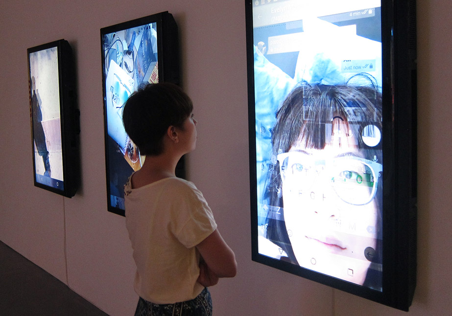 Woman examines a video collage portrait on a wall, showing a blend of a user's face, environment, and interface in user_is_present